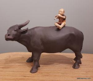 sculpture en terre cuite de Sandra Courlivant, enfant sur un buffle - profil